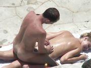 Et nudistpar knulder på stranden