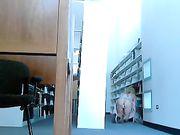 En pige er nøgen i biblioteket og masturbating