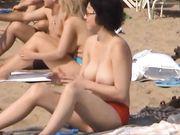Smukke kvinder med store bryster er topløse på stranden